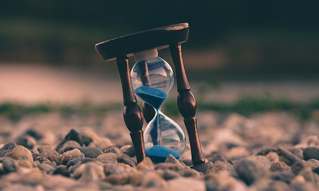 A small hourglass is set in the center foreground of a brown pebbly ground. The background is blurry. The hourglass is in motion and half full, with blue grains of sand.