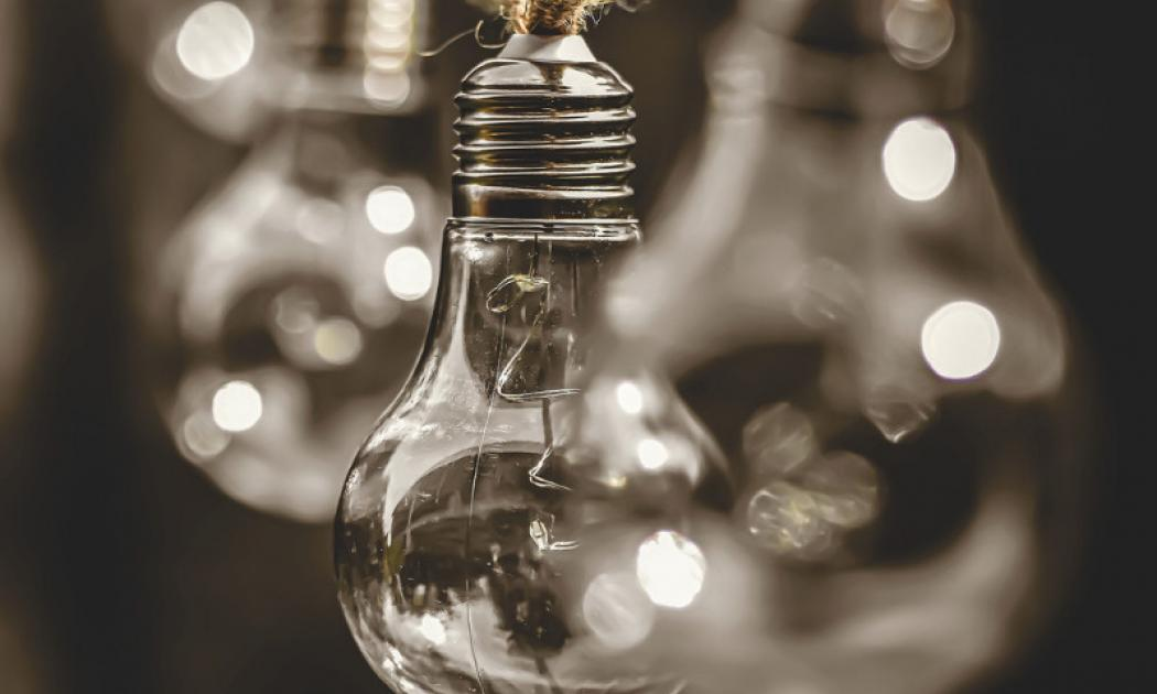 Light Bulbs Dangling From Rope Against Dark Background