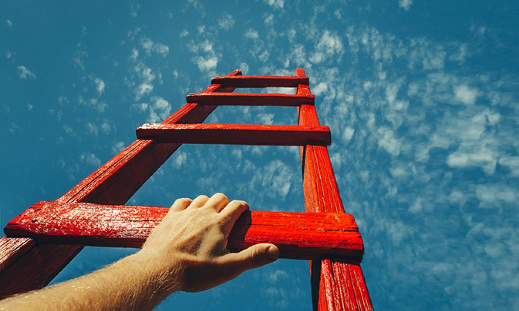 Hand Reaching For Red Ladder Leading To A Blue Sky