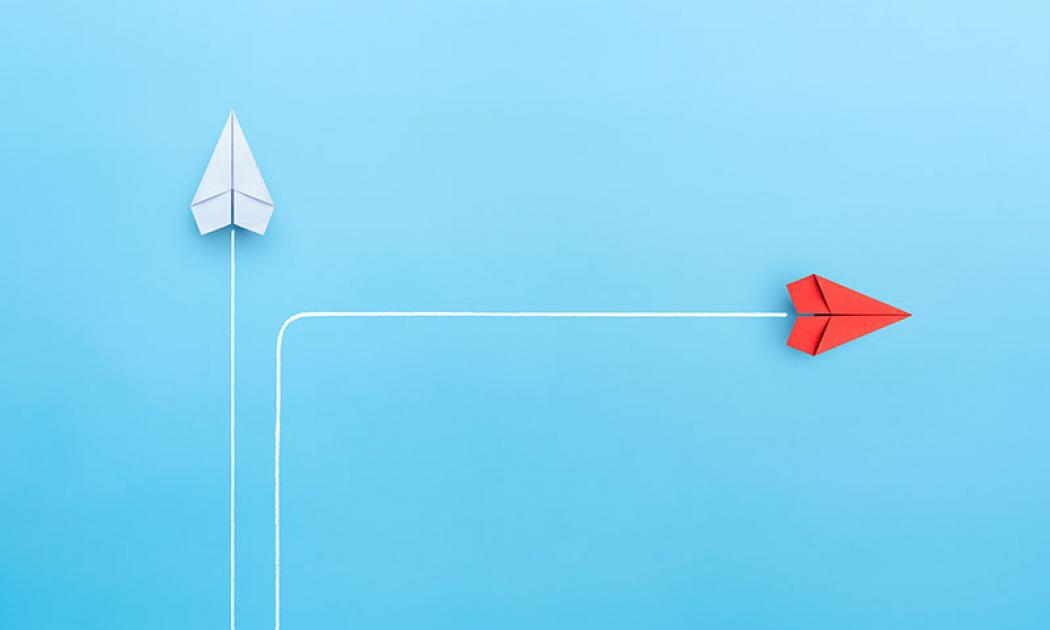 New normal concept with Red paper plane in new direction on blue background