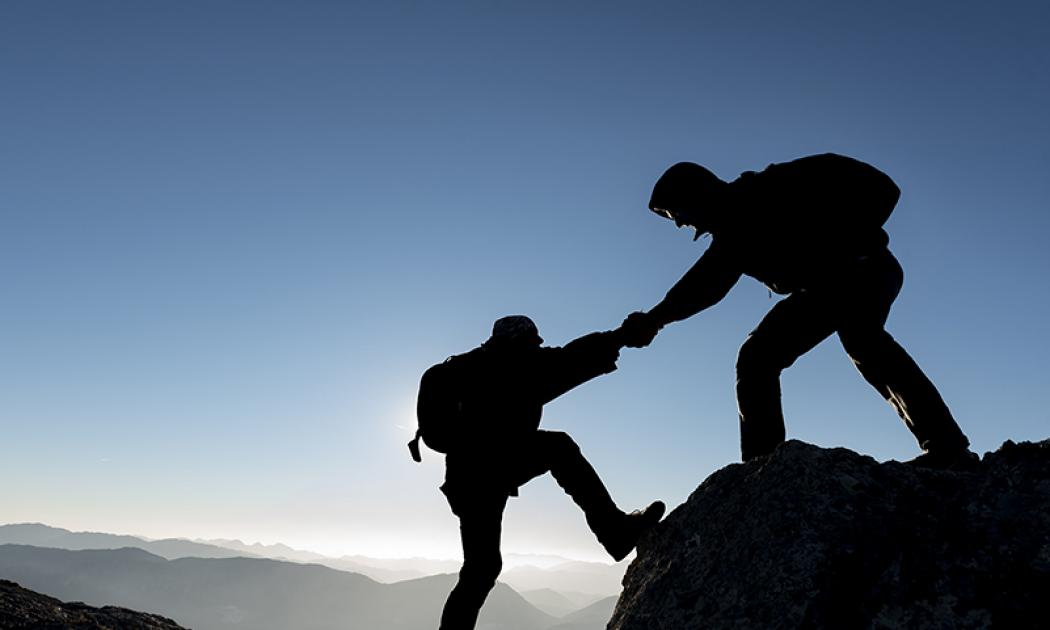 One climber offering a hand to another on top of a mountain with more mountains in the background