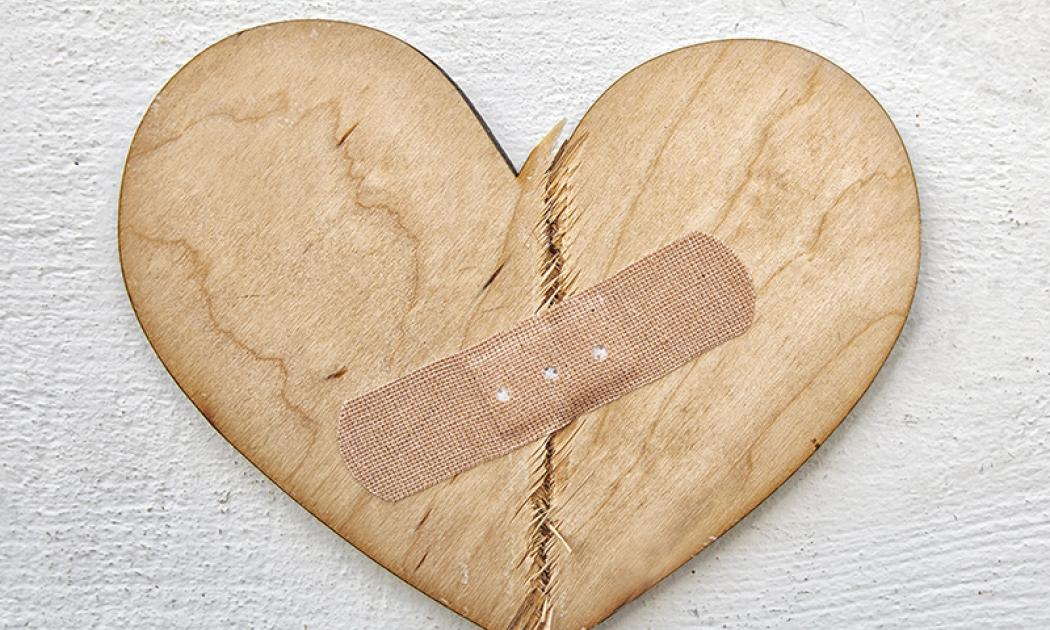 Broken wooden heart cutting board with bandaid