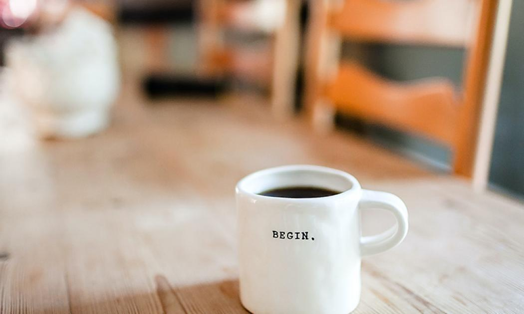 """Coffee cup with the word """"Begin"""" on a wooden table"""