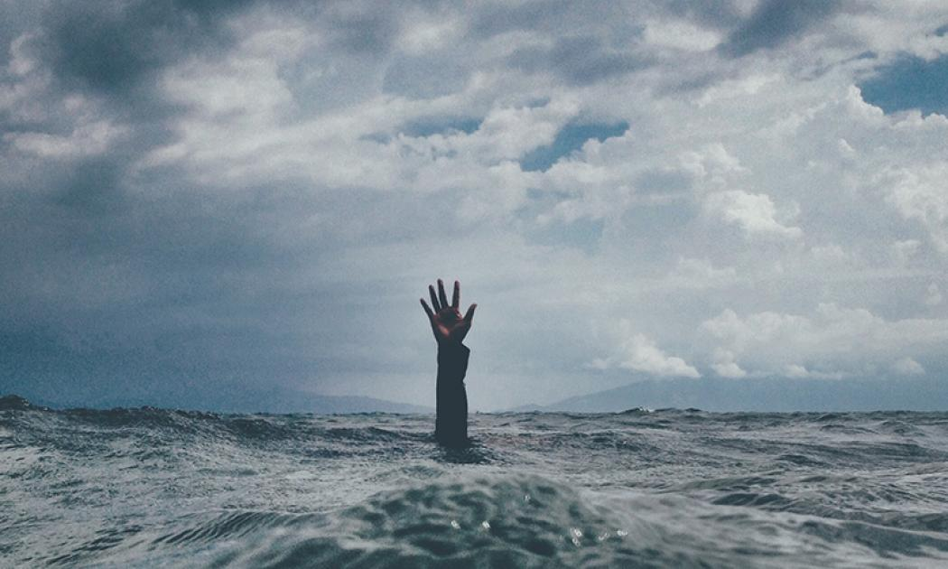Hand reaching out of a stormy ocean