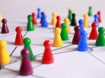 Primary colored game pieces on board with interconnecting lines