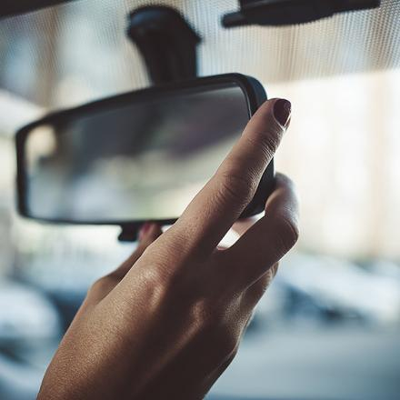 Hand adjusting a rearview mirror