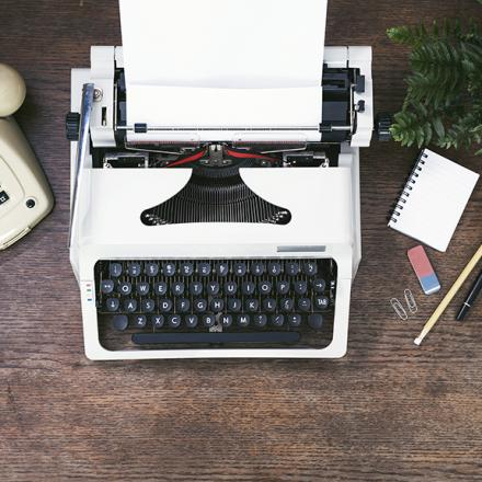 Phone, typewriter and office supplies on a wooden desk