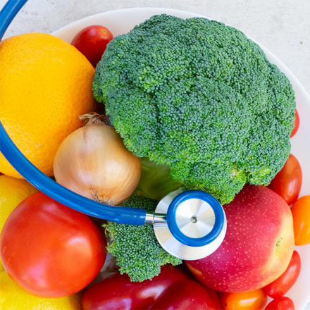 Stethoscope next to assorted vegetables on a plate