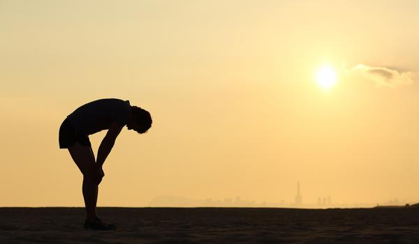 Silouette of a man bent over and catching his breath
