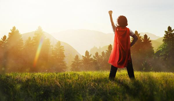 Young Girl Standing on a Mountain Top Field in Superhero Pose looking at the forrested mountains beyond