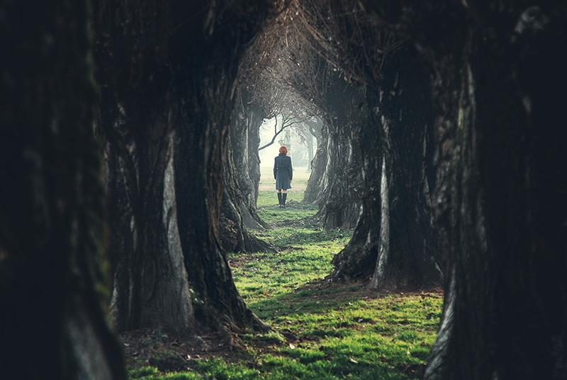 Woman walking into dark woods
